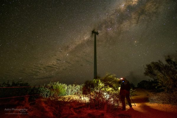 A ghostly figure and wind turbine at night. Image Credit: Roger Groom