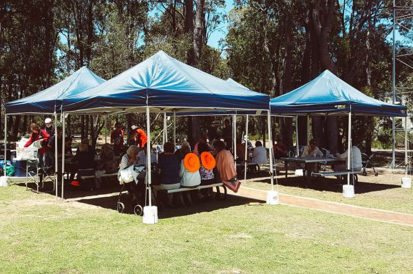 Day tour group having lunch under marquees. Image Credit: Matt Woods